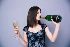 Woman holding two glass and drinking champagne from bottle Royalty Free Stock Photos