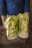 Woman holding two halves of the Chinese cabbage on the table. Vertical stock images