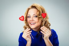 Woman holding two hearts on sticks Royalty Free Stock Photography