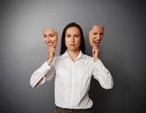 Woman holding two masks with different mood. Serious woman holding two masks with different mood Royalty Free Stock Photo