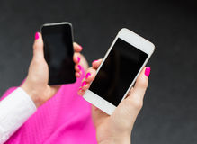 Woman holding two mobile phones Stock Photography