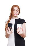Woman holding two mobile phones. Young redhead woman choose between two cell phones. Girl looks at mobile, selecting color - black or white. Comparing Royalty Free Stock Image