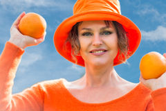 Woman holding  two  oranges. Woman in orange hat  holding  two oranges Royalty Free Stock Photos