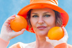 Woman holding  two  oranges. Woman in orange hat  holding a two oranges Royalty Free Stock Image