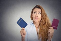 Woman holding two passports confused face expression Royalty Free Stock Image