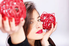 Woman holding two red balls Stock Photography