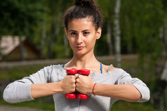 Woman holding two weights close to her Stock Photography