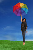 Woman Holding an Umbrella Falling from the Sky Royalty Free Stock Photography