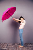 Woman holding umbrella over gray wall Stock Photography