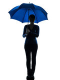 Woman holding umbrella smiling silhouette Stock Images