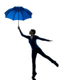 Woman holding umbrella wind blowing silhouette Stock Photos