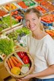 Woman holding up basket vegetables Stock Photo