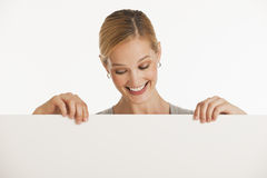 Woman holding up blank sign for copy space Royalty Free Stock Images