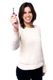Woman holding up a house key. Pretty young woman with a lovely smile holding up a house key in her hand as she proudly takes ownership of her new property Stock Image