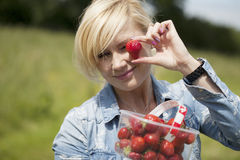 Woman holding up large ripe strawberry Stock Images
