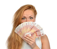 Woman holding up many cash money five thousand russian rubles no. Happy young woman holding up many cash money five thousand russian rubles notes in hand looking Royalty Free Stock Photos