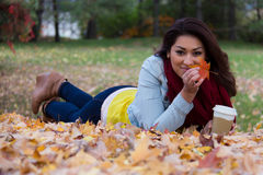 Woman holding up a maple leaf whle lying down on the ground Stock Photos