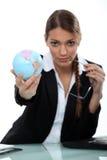 Woman holding up mini-globe Royalty Free Stock Photos