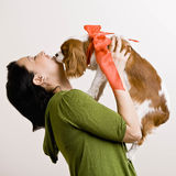 Woman holding up puppy. Devoted woman kissing pet dog with bow Royalty Free Stock Image