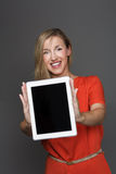 Woman holding up the screen of a tablet-pc. Pretty friendly young blond woman holding up the blank screen of a tablet-pc or notebook facing the camera with stock photo