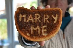 Woman holding up slice of burnt white toast, with the proposal Marry Me royalty free stock photography