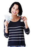 Woman holding US dollars bills and house model Royalty Free Stock Image