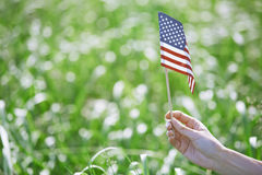 Woman holding US flag in a grassland Stock Images
