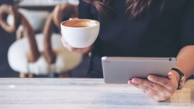 Woman holding and using tablet pc while drinking coffee stock photos