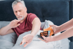 Woman holding various pills for sick husband in hands royalty free stock images