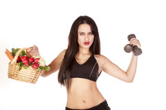 Woman holding vegetables and weights up. A woman is holding up a basket of vegetables and some weights Stock Image