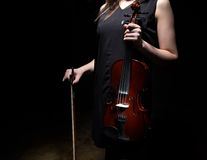 Woman holding violin and fiddlestick. On black background Royalty Free Stock Photo