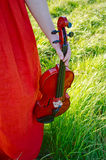 A woman holding a violin in nature. A young womans arm holding a violin, surrounded by nature Royalty Free Stock Photo