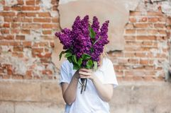 Woman holding a vivid bunch of lilac flowers against brick wall stock images