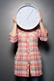 Woman holding wall clock infront of her face Stock Image