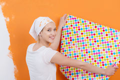 Woman Holding Wallpaper Against Orange Colored Wall Royalty Free Stock Photography
