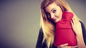 Woman holding warm red hot water bottle Stock Photography