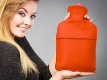 Woman holding warm red hot water bottle Royalty Free Stock Photos