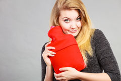 Woman holding warm red hot water bottle Stock Photo