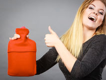 Woman holding warm red hot water bottle Stock Images