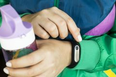 Women`s fitness - water and smart watches - gadgets and equipment for sports. A woman is holding a water bottle for fitness and a fitness bracelet. In a sports Royalty Free Stock Images