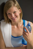 Woman holding water bottle in locker room Stock Image