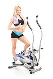Woman holding water on a cross trainer machine Royalty Free Stock Photos