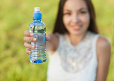 Woman holding water. Portrait half face of young woman holding water bottle at summer green park Royalty Free Stock Image