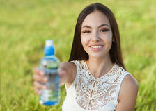 Woman holding water. Portrait half face of young woman holding water bottle at summer green park Royalty Free Stock Photos