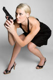 Woman Holding Weapon. Blond spy woman holding weapon Royalty Free Stock Photography