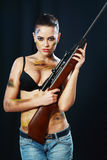Woman holding weapon. Beautiful sexy woman holding weapon over dark background Royalty Free Stock Photos