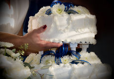 Woman holding wedding cake. A woman holds a layer of wedding cake Royalty Free Stock Image