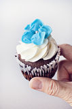Woman holding wedding cupcake. Decorated with blue fondant flower Stock Photos