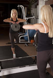 Woman holding weight in mirror. A woman lifting a weight showing off her strength and balance Royalty Free Stock Images