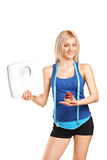 Woman holding a weight scale and a cake Royalty Free Stock Photo